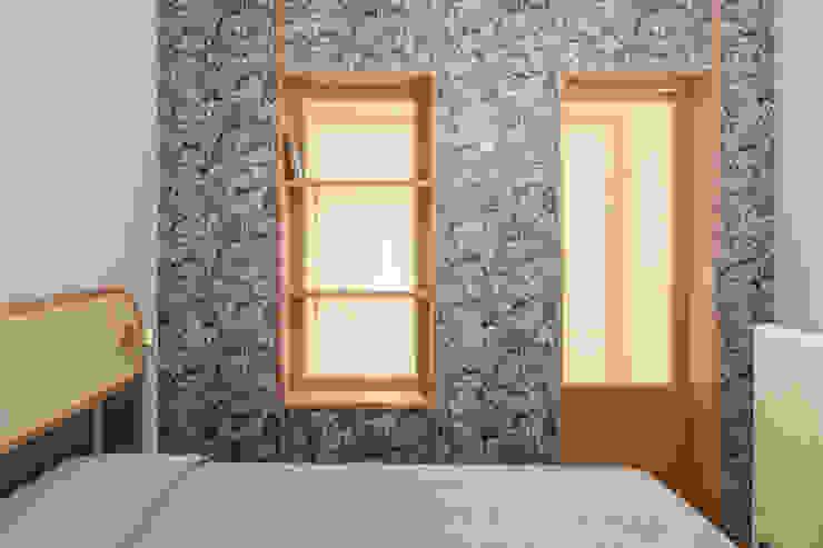 La cabina armadio con divisorio in legno, carta da parati e paglia di vienna Camera da letto eclettica di PLUS ULTRA studio Eclettico Legno Effetto legno