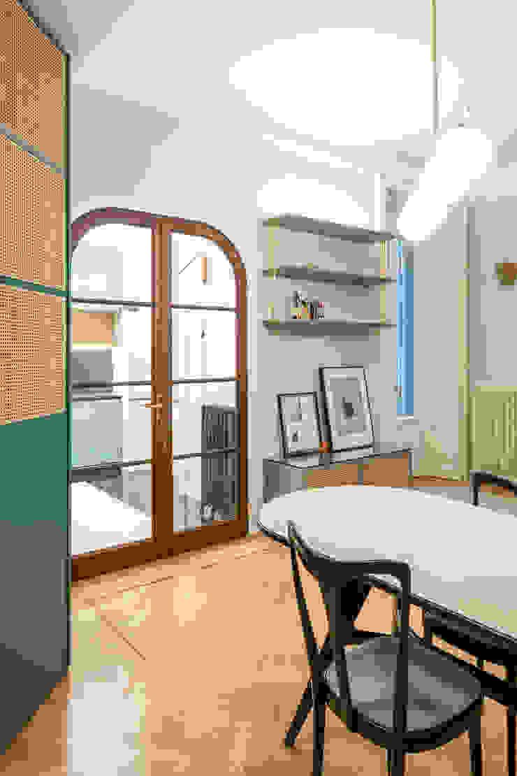 La zona pranzo, con la vetrata verso la cucina Sala da pranzo eclettica di PLUS ULTRA studio Eclettico