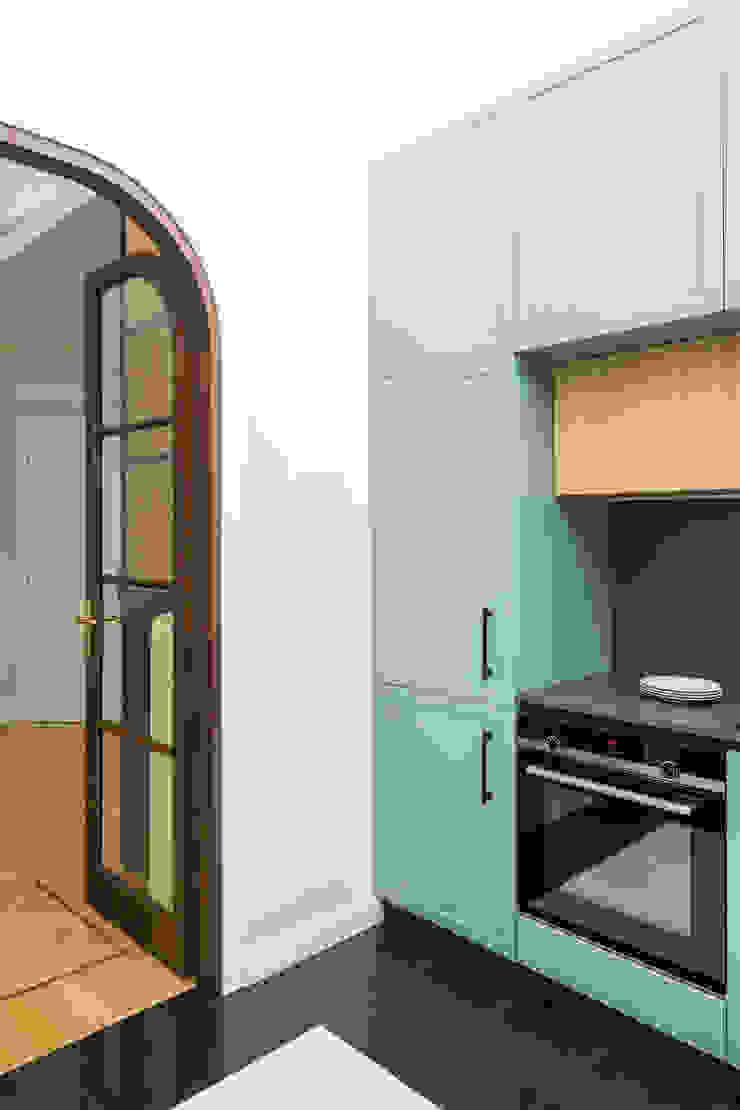 Vista della cucina verso il soggiorno, attraverso la porta a vetri realizzata su disegno di PLUS ULTRA studio Eclettico