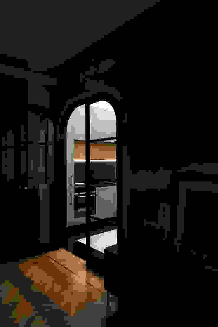 Vista della cucina dal soggiorno, attraverso la porta a vetri realizzata su disegno di PLUS ULTRA studio Eclettico