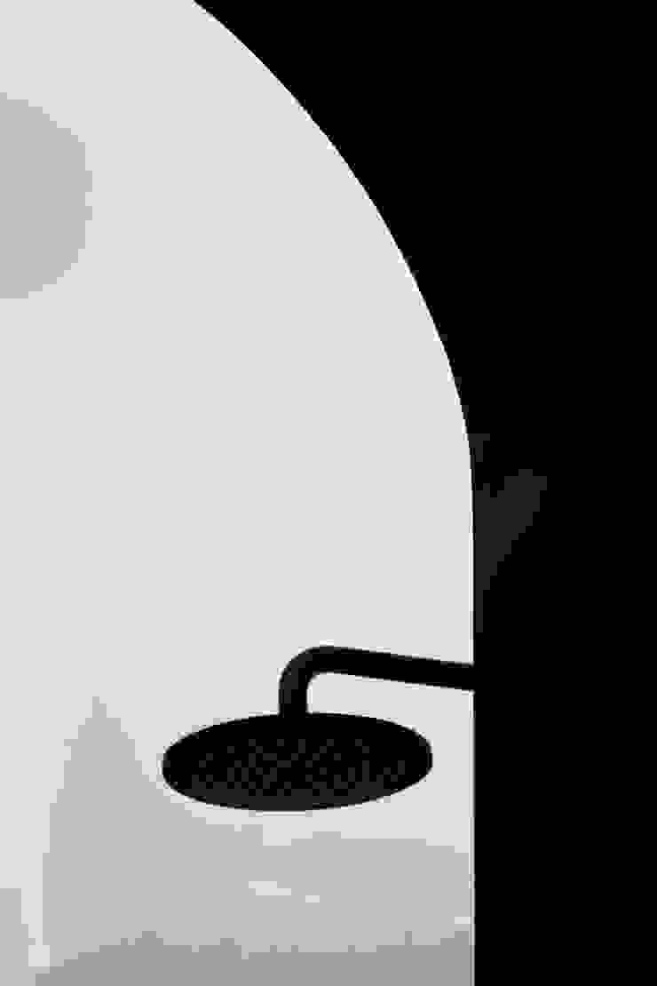 Dettaglio dell'arco della doccia e della rubinetteria nera Bagno eclettico di PLUS ULTRA studio Eclettico