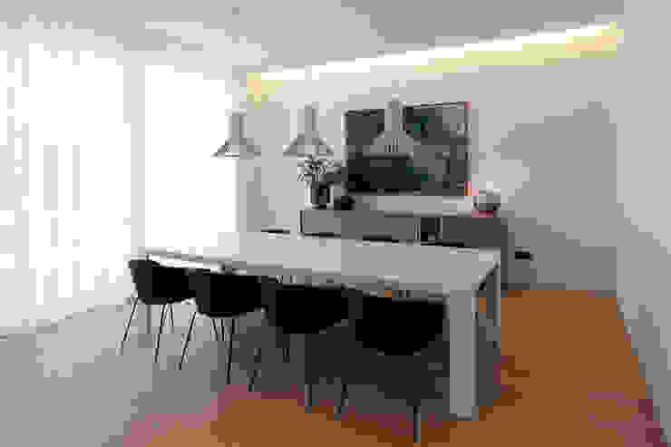 Comedor con una mesa generosa y tres luminarias suspendidas MANUEL GARCÍA ASOCIADOS Comedores de estilo moderno Blanco