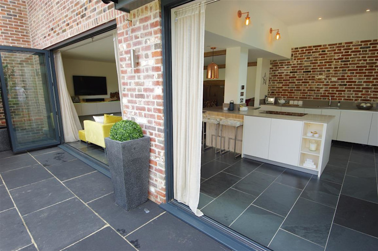 Open kitchen and living room with bi-fold doors PTC Kitchens Cucina moderna Effetto legno