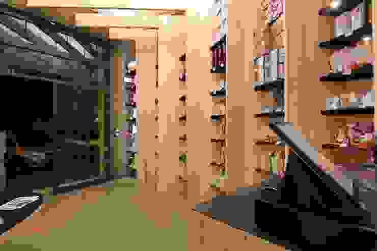 Lo spazio espositivo dal bancone Spazi commerciali moderni di ibedi laboratorio di architettura Moderno Legno Effetto legno