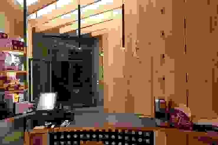 Lo spazio espositivo dal bancone ed il sotto bancone in ferro. ibedi laboratorio di architettura Bar & Club moderni Legno Ambra/Oro