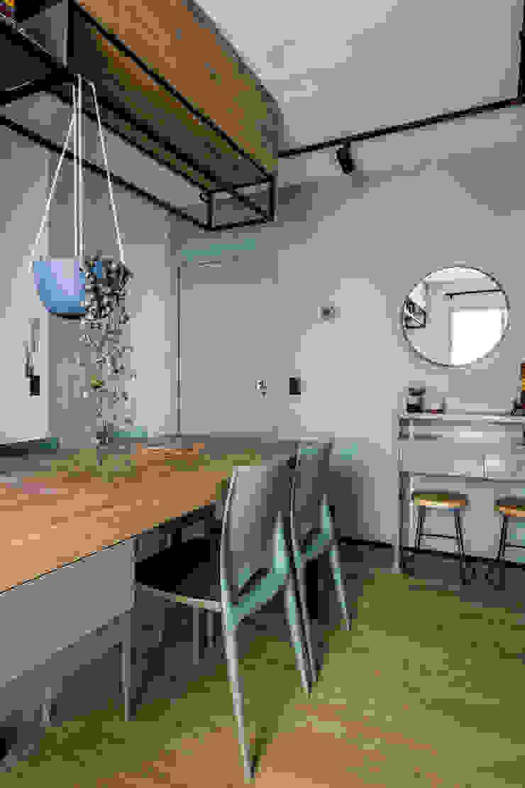 O que divide a sala da cozinha ´é uma mesa de janta para 4 pessoas Studio Elã Salas de jantar industriais Madeira Verde
