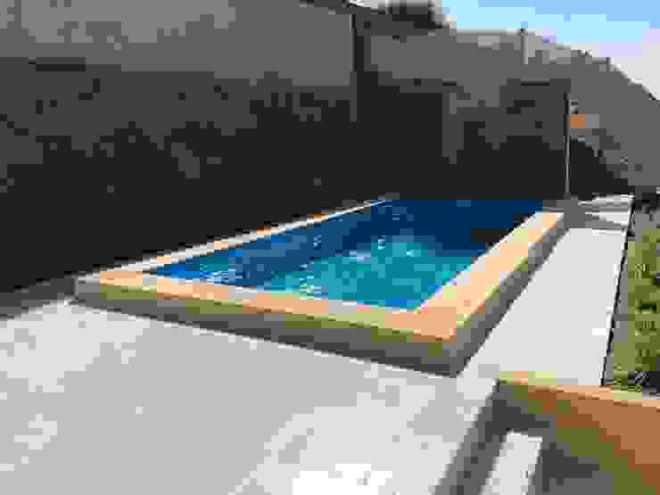 Piscina con muro y Cascada de agua de Triptico Diseño y Construcción Mediterráneo