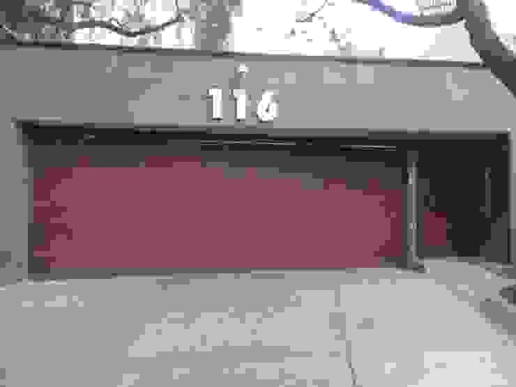 Puerta plegadiza de cuatro hojas, forradas con duela de aluminio tono madera, en unión de puerta peatonal independiente, automatizadas. PUERTAS AUTOMÁTICAS GROSSMANN Puertas de entrada Aluminio/Cinc Acabado en madera