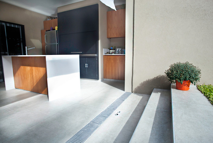 La mixtura entre el quincho y el jardin de la casa, un juego de desniveles de Ba75 Atelier de Arquitectura Moderno
