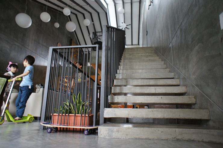 Wall protruded concrete slab steps, complimented with vertical sleek metal railing N O T Architecture Sdn Bhd Stairs