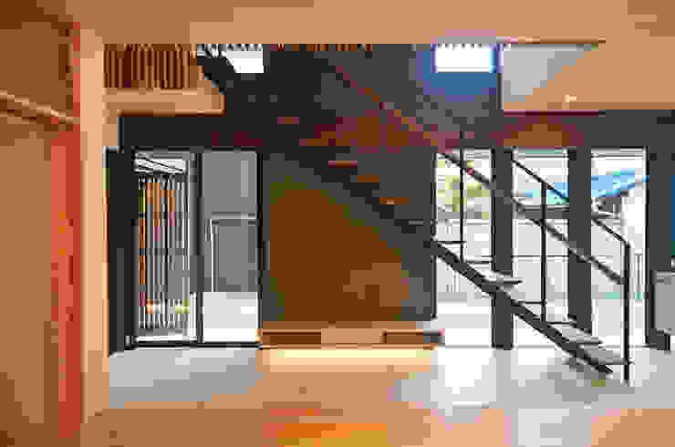 土間吹抜けにかかる階段 大塚高史建築設計事務所 モダンデザインの リビング 木 灰色