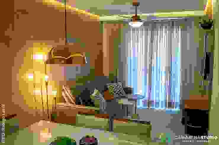 Sala integrada estar e jantar com iluminação diferenciada Camarina Studio Salas de estar modernas Ambar/dourado
