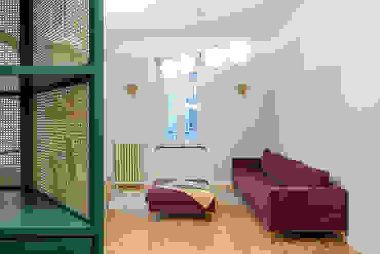 La zona living, con un divano e pouff disegnati su misura e realizzati da un artigiano PLUS ULTRA studio Soggiorno eclettico