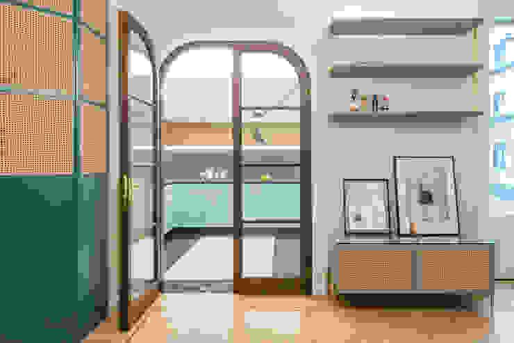 La porta a vetri in rovere tinto, realizzata su disegno, che divide la zona giorno dalla cucina PLUS ULTRA studio Soggiorno eclettico