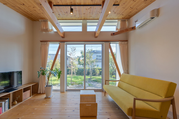 リビングを通して庭を見る アース・アーキテクツ一級建築士事務所 カントリーデザインの リビング 無垢材 木目調