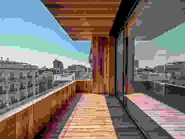 Terraza en madera Ipe con barandilla retroiluminada de vidrio GOS ARCH·LAB Balcones y terrazas de estilo moderno Madera maciza Acabado en madera