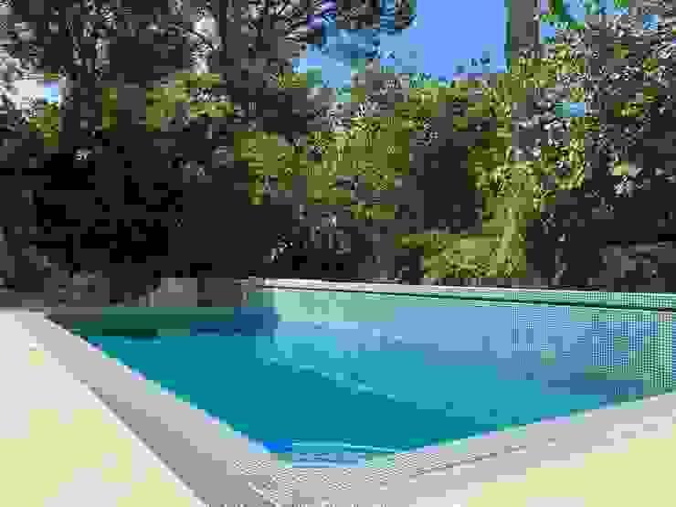 Piscina de desborde con muro lateral donde se alberga haz de luz y cascada de agua Gomez-Ferrer arquitectos Piscinas de jardín