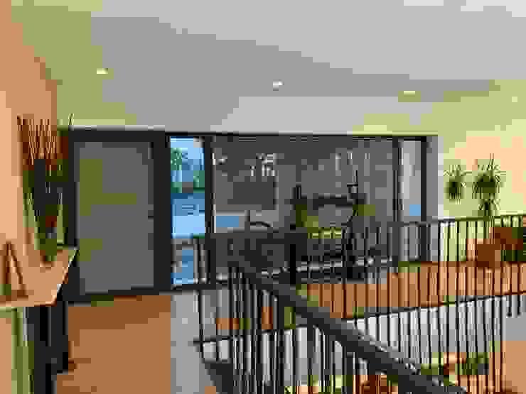 Hall de entrada con puerta aplacada en tablero de cemento y virutas tipo viroc. Gran cristalera con visión de la entrada desde la calle y aparcamiento Gomez-Ferrer arquitectos Pasillos, vestíbulos y escaleras de estilo moderno