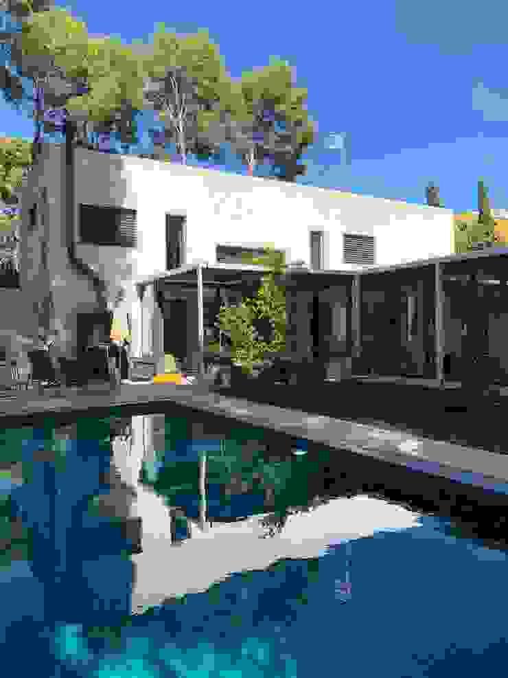 Piscina con zona de césped natural y corredor acristalado de la vivienda alrededor del espacio Gomez-Ferrer arquitectos Piscinas de jardín