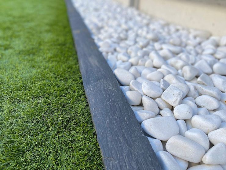 Garden with artificial grass and white pebbles separated by a slate border. Canteras el Cerro 花園配件與裝飾品 大理石 White