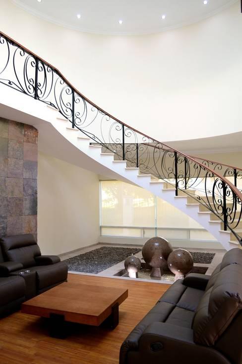 Casa Colomos: Pasillos y recibidores de estilo  por Excelencia en Diseño