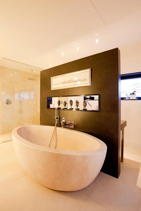 Baño en la piedra: Baños de estilo  de IPUNTO INTERIORISMO