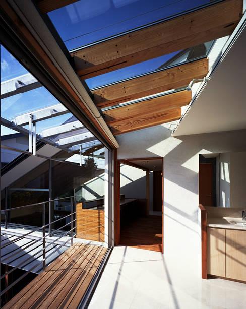 光を抱く家: 西島正樹/プライム一級建築士事務所 が手掛けたサンルームです。