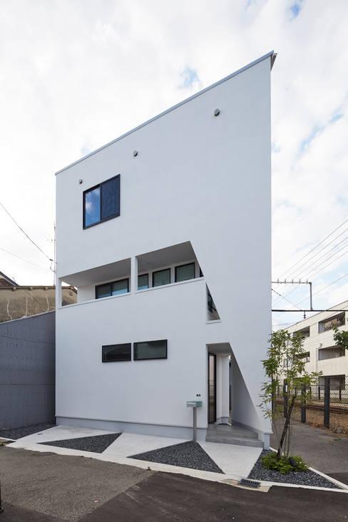 3角敷地に3角な3階建の家: 一級建築士事務所 株式会社KADeLが手掛けた木造住宅です。