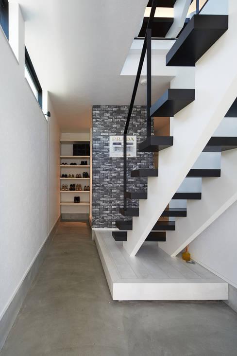 3角敷地に3角な3階建の家: 一級建築士事務所 株式会社KADeLが手掛けた廊下 & 玄関です。
