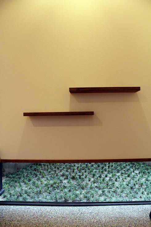 玄関飾り棚と坪庭: 秀田建築設計事務所が手掛けた庭です。