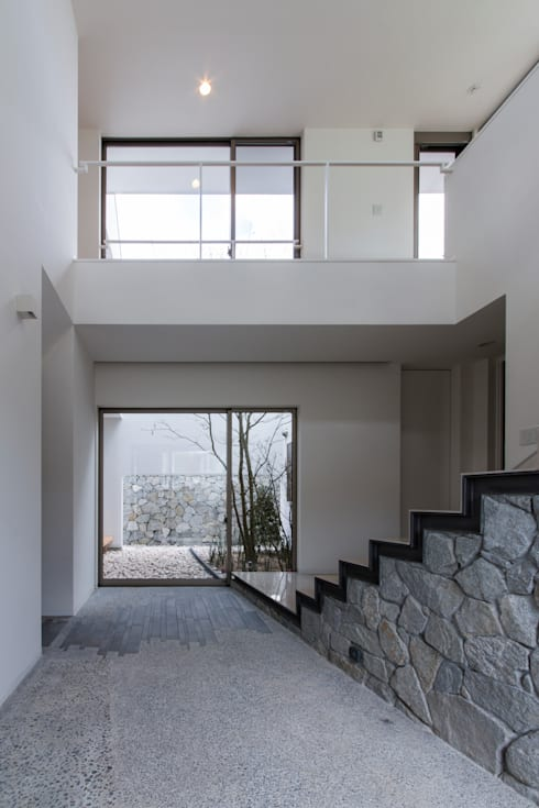 The House creates open land scape: Kenji Yanagawa Architect and Associatesが手掛けた廊下 & 玄関です。