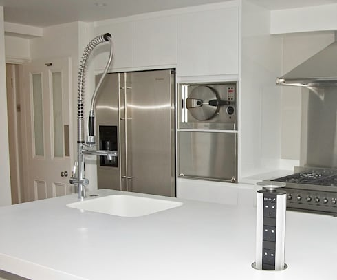 White gloss kitchen with Corian worktops: modern Kitchen by Greengage Interiors Limited