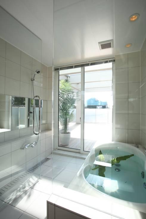 サッシを開ければウッドデッキ: TERAJIMA ARCHITECTSが手掛けた浴室です。