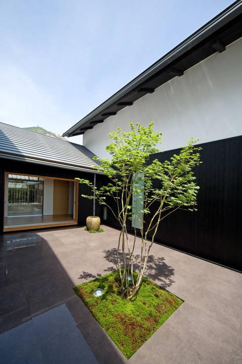 2世帯間の緩衝体となる中庭: 株式会社古田建築設計事務所が手掛けた庭です。