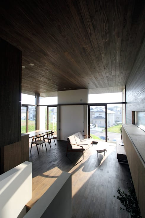 丘の上の二世帯住宅: 時空遊園 JIKOOYOOEN ARCHITCTSが手掛けたリビングです。