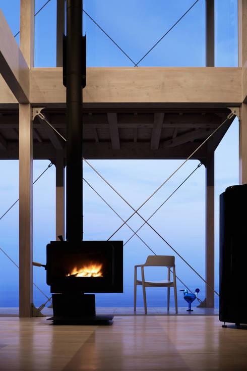 薪ストーブ夕景~熱海伊豆山Yさんの家: atelier137 ARCHITECTURAL DESIGN OFFICEが手掛けたリビングです。