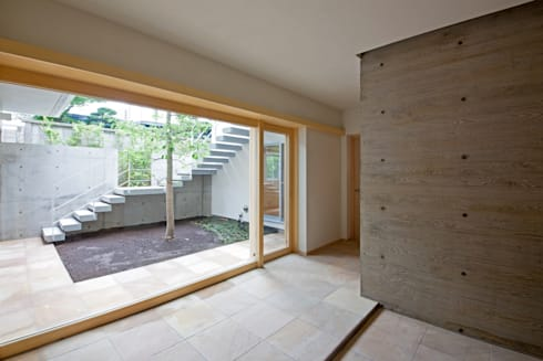 中庭と一体の玄関: 根岸達己建築室が手掛けた庭です。