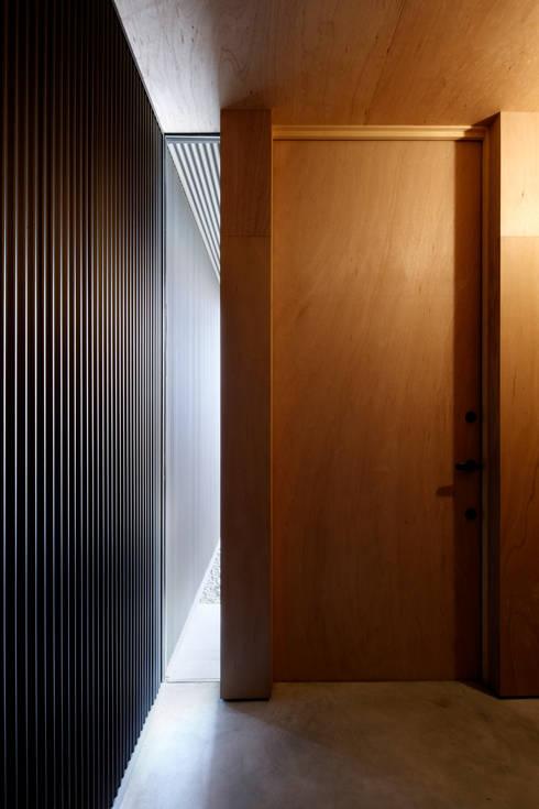 玄関ホール: 道家洋建築設計事務所が手掛けた窓です。