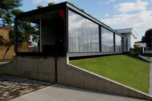 Acesso de veículos e detalhe da base de apoio do pavilhão em concreto aparente.: Espaços comerciais  por JOBIM CARLEVARO arquitetos