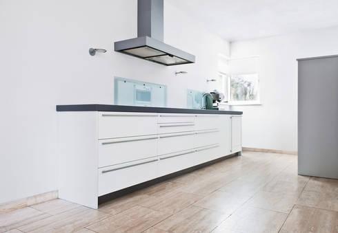 Strakke witte keuken met travertin vloer: moderne Keuken door Interieurvormgeving Inez Burvenich