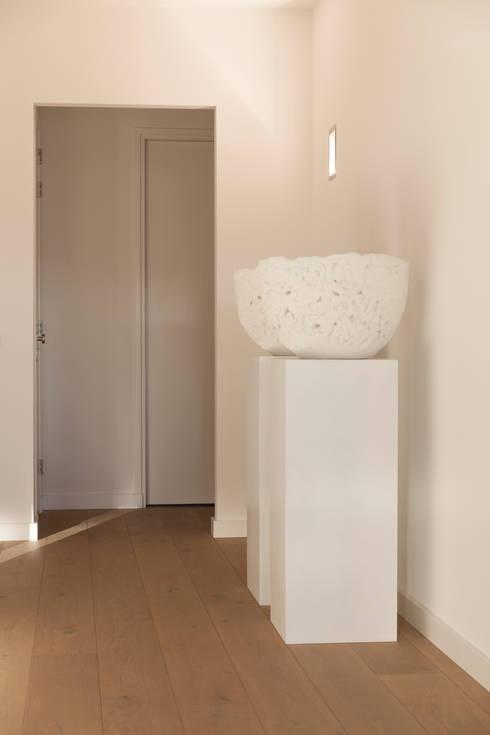 zwart - wit penthouse hal:  Gang en hal door Interieurvormgeving Inez Burvenich