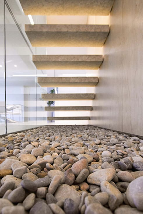 Vista trasera de la escalera de piedra con las piedras naturales - Casa Moncofa - Chiralt Arquitectos : Pasillos y vestíbulos de estilo  de Chiralt Arquitectos
