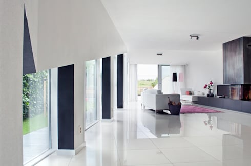 zwarte muren framen het uitzicht naar buiten: moderne Woonkamer door IJzersterk interieurontwerp