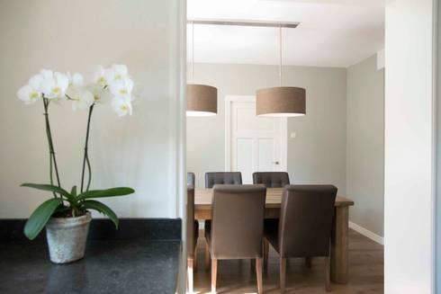 Eettafel met gecapitonneerde stoelen en stoffen lampenkappen: landelijke Eetkamer door Hemels Wonen interieuradvies en ontwerp