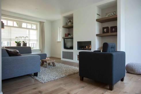 Overzicht van de woonkamer met zicht op de prachtige gashaard: landelijke Woonkamer door Hemels Wonen interieuradvies en ontwerp