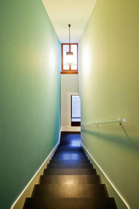 Die Kaskadentreppe erschließt einen überraschend proportionierten, hohen und schmalen Treppenraum:  Flur & Diele von Eingartner Khorrami Architekten BDA