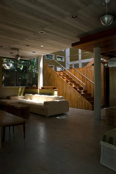 Santiago | casa praia: Salas de estar tropicais por ARQdonini Arquitetos Associados
