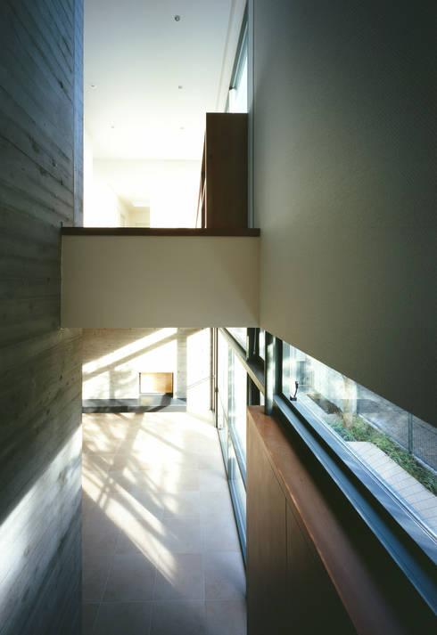 階段からリビングルームを見る: 山崎壮一建築設計事務所が手掛けた廊下 & 玄関です。