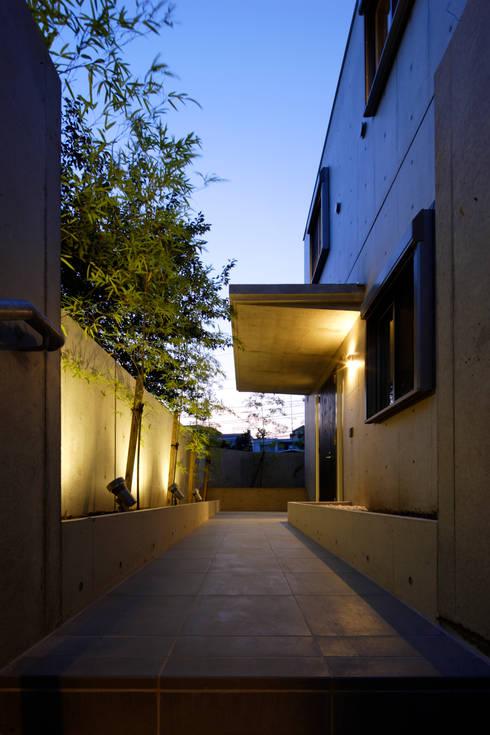 玄関アプローチ: 鈴木賢建築設計事務所/SATOSHI SUZUKI ARCHITECT OFFICEが手掛けた庭です。