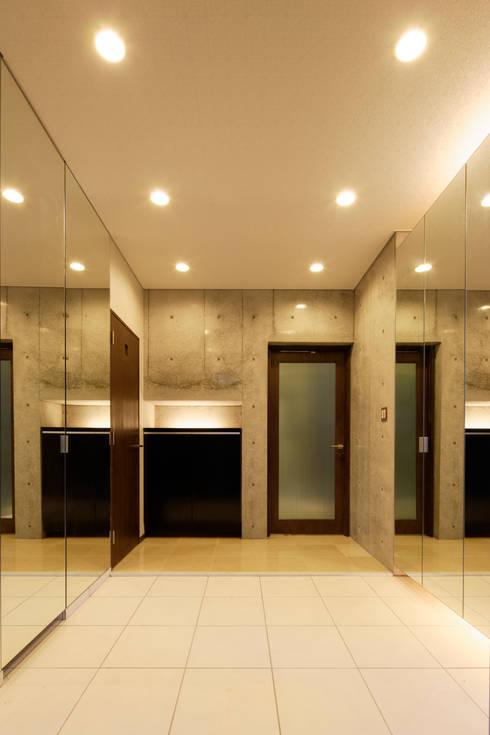 シューズクローゼットの扉を鏡貼りとした開放的な玄関: 鈴木賢建築設計事務所/SATOSHI SUZUKI ARCHITECT OFFICEが手掛けた廊下 & 玄関です。
